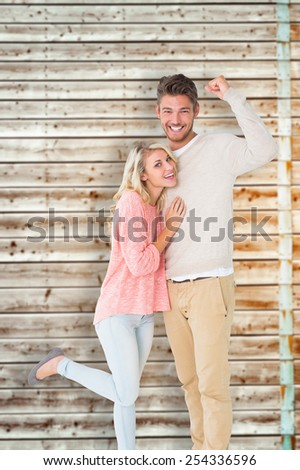 Attractive couple smiling and cheering against faded pine wooden planks - stock photo