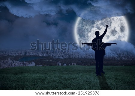 Attractive couple smiling and cheering against large moon over city - stock photo