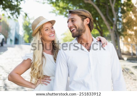 Attractive couple smiling at each other on a sunny day in the city