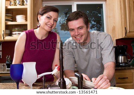 Attractive couple smiling while doing dishes in their kitchen. Horizontally framed shot. - stock photo