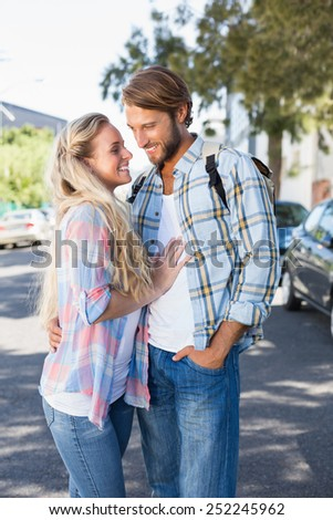 Attractive couple standing and hugging on a sunny day in the city - stock photo