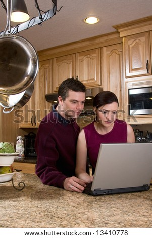 Attractive couple standing in their kitchen and reviewing something on their laptop screen together. Both are looking at the screen with a serious expression. Vertically framed shot. - stock photo
