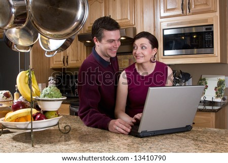 Attractive couple standing in their kitchen and reviewing something on their laptop screen together. Both are smiling and looking at each other. Horizontally framed shot. - stock photo