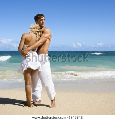 Attractive couple standing on Maui, Hawaii beach holding eachother.