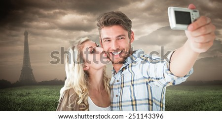 Attractive couple taking a selfie together against paris under cloudy sky - stock photo