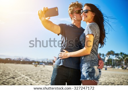 attractive couple taking selfie under the intense sun on the beach together with lens flare and shot with selective focus - stock photo