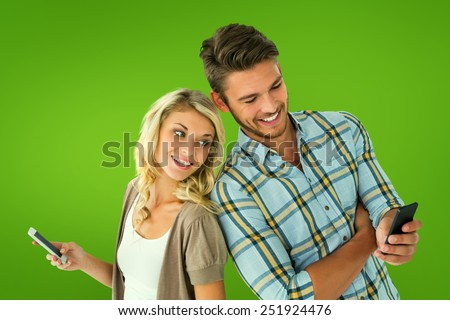 Attractive couple using their smartphones against green vignette - stock photo