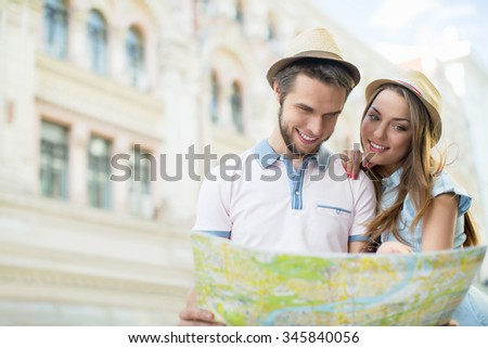 Attractive couple with a map on the street - stock photo