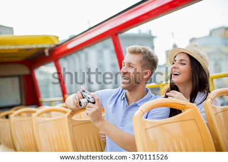 Attractive couple with camera in a tour bus - stock photo