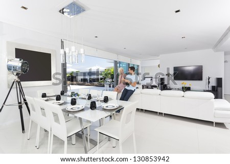 Attractive couple with champagne bottle in luxury apartment - stock photo