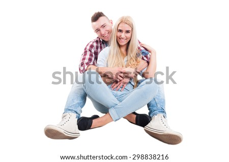 Attractive couple with handsome boyfriend and beautiful blonde girlfriend sitting isolated on white studio background - stock photo