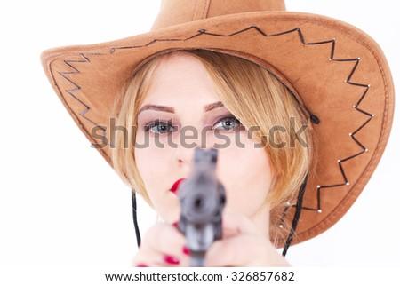 Attractive cowboy woman aiming a gun  - stock photo