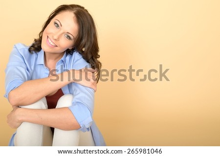 Attractive Cute Young Woman Sitting on the Floor Wearing a Blue Shirt and White Jeans Looking Happy and Relaxed - stock photo
