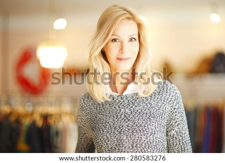 Attractive designer woman standing in her clothing store while looking at camera and smiling. Small business. - stock photo