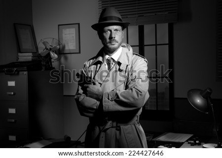Attractive detective holding a revolver with retro office on background, film noir. - stock photo