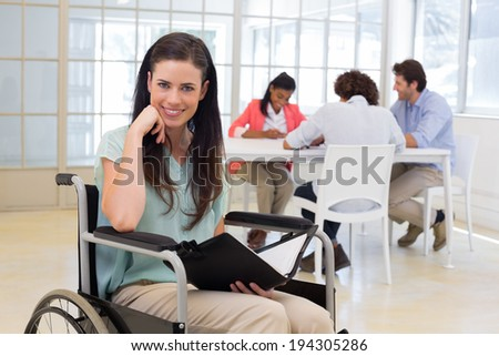 Attractive disabled businesswoman smiling at the camera while her coworkers are also working hard in the background - stock photo