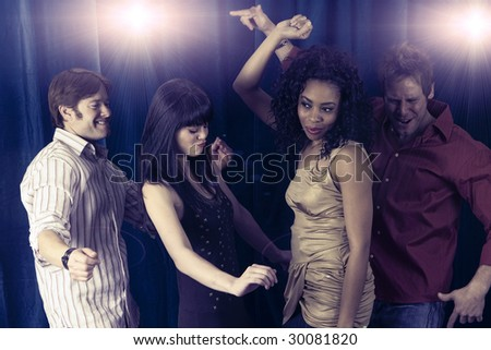 Attractive diverse friends dancing at a club - stock photo