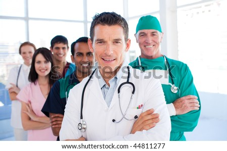 Attractive doctor standing with his colleagues in a hospital - stock photo