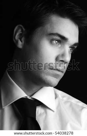 attractive dramatic masculine low key picture of a handsome businessman - stock photo