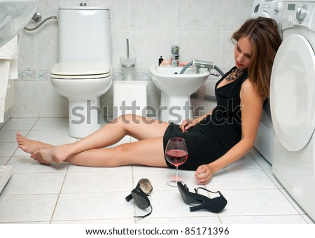 attractive drunk woman in her bathroom with glass of red wine - stock photo