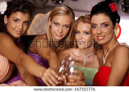 Attractive elegant girls celebrating with champagne, smiling. - stock photo