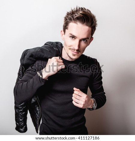 Attractive elegant man in black t-shirt and leather jacket in his hands posing on light gray studio background. - stock photo