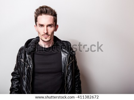 Attractive elegant man in stylish black leather jacket posing on light gray background. - stock photo