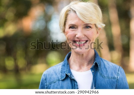 attractive elegant mid age woman standing outdoors - stock photo