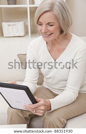 Attractive elegant senior woman using a tablet computer at home. - stock photo