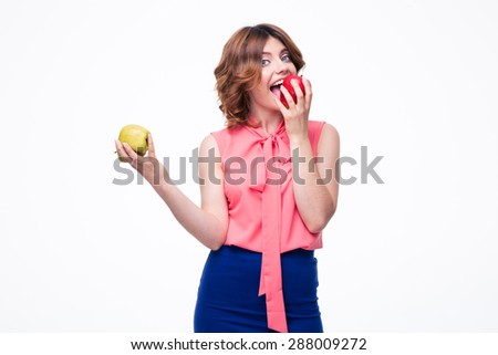 Attractive elegant woman eating apple isolated on a white backgorund. Looking at camera - stock photo