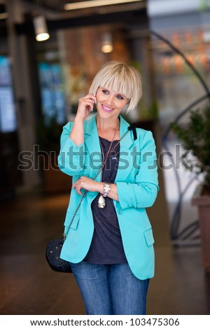 attractive elegant woman talking to mobile phone in shopping mall