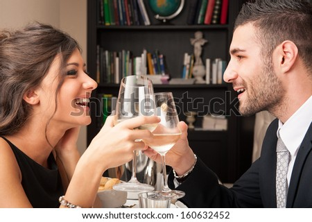 Attractive elegant young couple drinking to each others celebrating at the restaurant. - stock photo