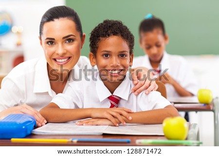 attractive elementary school teacher and students in classroom - stock photo