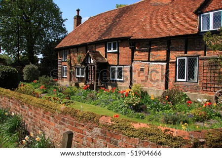 Attractive English medieval brick and timber cottage with flower garden - stock photo