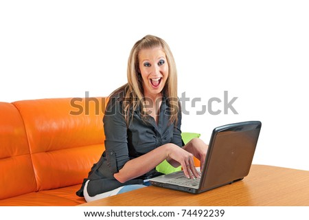 Attractive excited young woman sitting at home using a laptop - stock photo