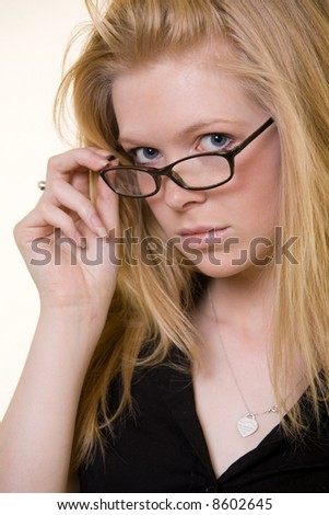 Attractive face of young blond woman wearing dark framed eye glasses