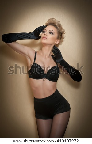 Attractive fair hair model with pantyhose and black gloves posing provocatively. Fashion portrait of sensual short hair blonde, studio shot. Sensual female in pantyhose, bra and gloves posing. - stock photo