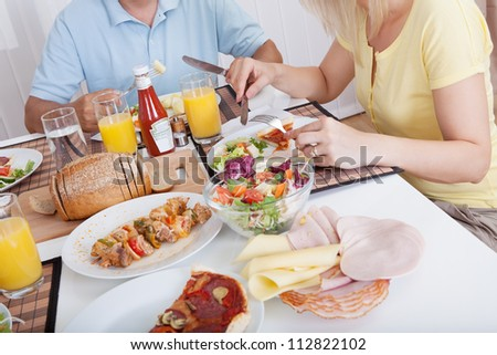 Attractive family enjoying a healthy meal together seated around the table - stock photo