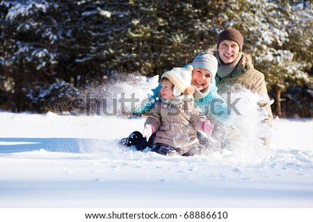 Attractive family having fun in fluffy snow - stock photo