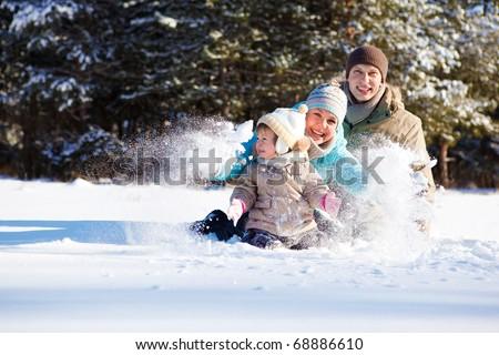 Attractive family having fun in fluffy snow - stock photo