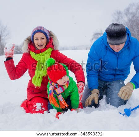Attractive family of three having fun in a snow winter park