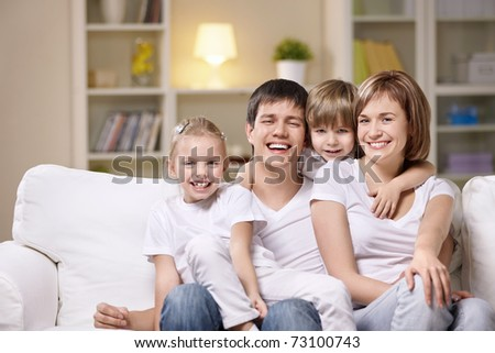 Attractive family with children at home in the evening - stock photo