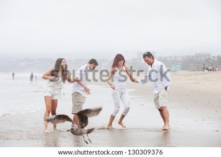 Attractive family with teens having fun on the beach at Santa Monica Ca as a bird flies by