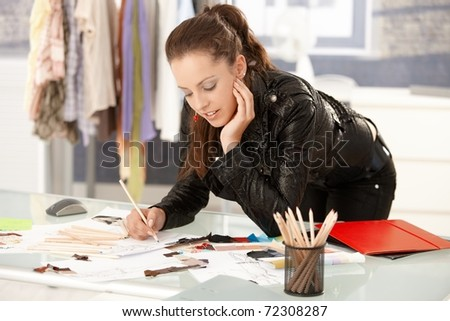 Attractive fashion designer working in office, leaning on desk, drawing.? - stock photo