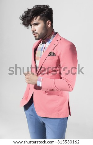 attractive fashion male model dressed elegant - casual posing against grey wall - stock photo