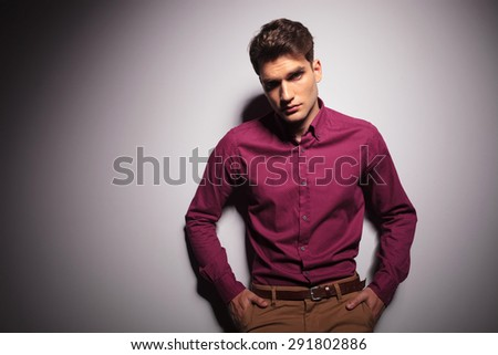 Attractive fashion man holding his hands in pockets while looking at the camera.