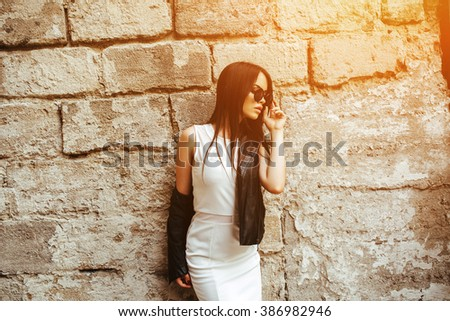 Attractive fashion woman in white dress with sunglasses posing near white wall - stock photo