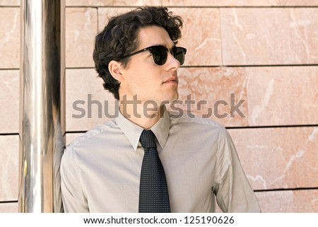 Attractive fashionable businessman wearing an elegant tie and shades, leaning on a metallic pole in a modern stone office building in the city.