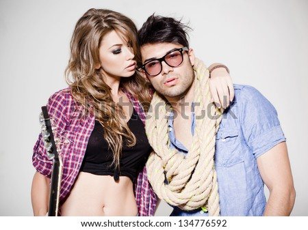 attractive fashionable couple wearing jeans posing dramatic - stock photo