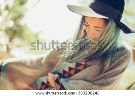 Attractive fashionable girl in a hat and poncho walking outdoor - stock photo